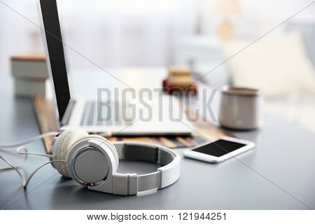 Headphones, phone and laptop on white table against defocused background