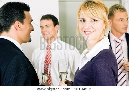 People in business outfit celebrating something in the office or at a gathering, maybe they toast on a successful deal or something the like