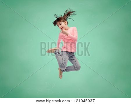 school, education, childhood, freedom and people concept - happy little girl jumping in air over green school chalk board background