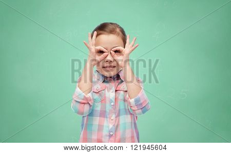 childhood, fun, school, education and people concept - happy little girl making faces over green chalk board background