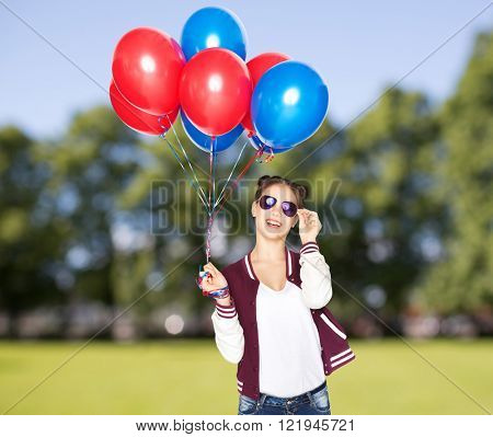 people, teens, holidays, party and summer concept - happy smiling pretty teenage girl in sunglasses with helium balloons over park background