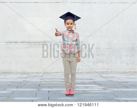 childhood, school, education, learning and people concept - happy girl with in bachelor hat or mortarboard showing thumbs up over urban concrete background