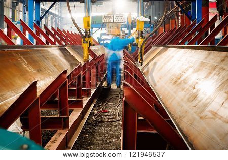 Workers on the assembly-line metal processing plant