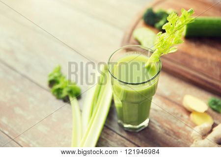 healthy eating, organic food and diet concept - close up of fresh green juice with celery on wooden table