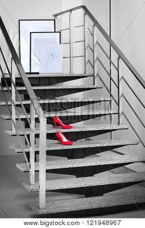 Red stiletto heels on modern stairs in office