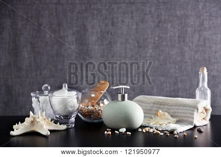 Bathroom set with dispenser, wooden comb and towel on grey background