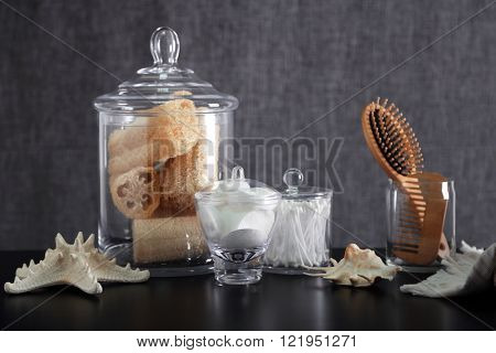 Bathroom set with wooden comb, wisps and sponges on grey background