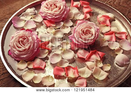 Pink and white rose petals in silver bowl with water on wooden background
