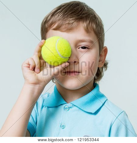 Children. Close up portrait of a cute little boy holding a tennis ball at the eye, gray background