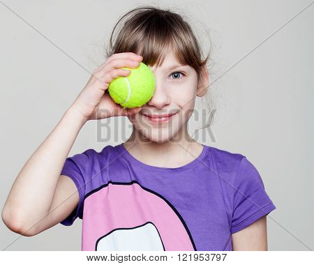 Children. Close up portrait of a cute girl holding a tennis ball at the eye smiling gray background
