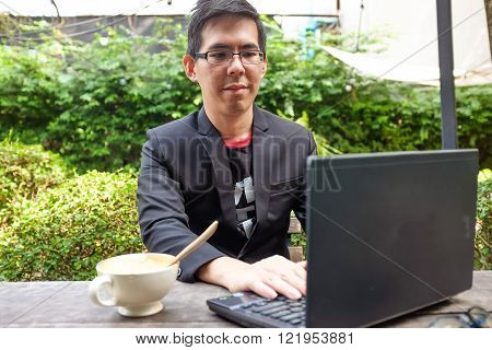 Handsome Asian Young Man Working On Laptop At Coffe Shop