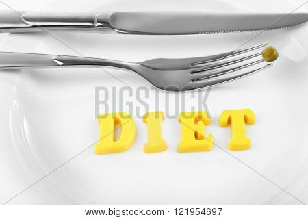 Silver fork and knife with single pea and word DIET on white plate closeup