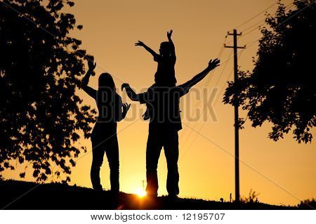 Family having a walk at sunset, the child sitting on his father's shoulders waving at the viewer; the whole scene is shot back lit, very tranquil and peaceful