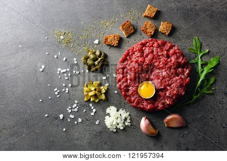 Beef tartare served with an egg yolk on a grey surface, top view