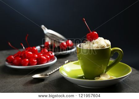 Chocolate cake in a green mug served with two plates of cherries and chocolates, close up
