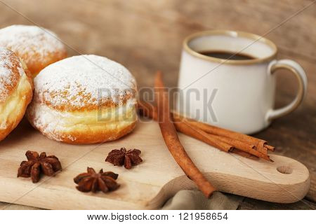 Delicious sugary donuts with spices and cup of coffee on wooden cutting board closeup
