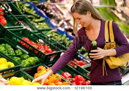 woman in a supermarket at the vegetable shelf shopping for groceries, she is choosing