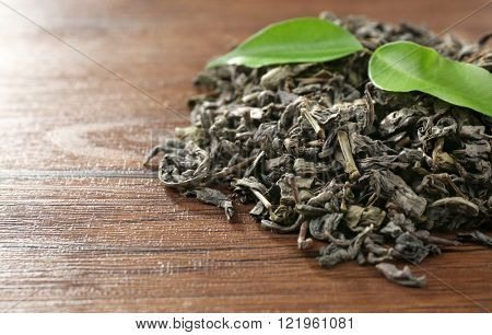 Dry tea with green leaves on wooden table background