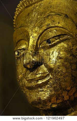 Buddha statue at Wat Bang Ko Theppasak, Amphawa Thailand covered with gold leaf placed by temple visitors wishing to make merit.