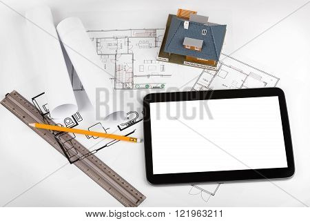 blank tablet and house scale model on architectural blueprints