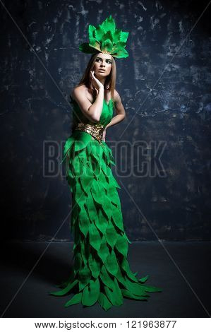 Beautiful sexy young girl woman lady model posing with hand in long paper green dress hair eccessories golden belt in fashion photo studio grey background