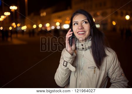 Euphoric woman using her smart phone and smiling to good news phone call.Happy woman talking with friend on a smart phone on a city street.Communication with people,distant relationship connections