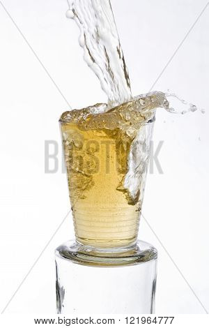 Tea drinks poured vigorously overflowing splashing from a glass, on a white background