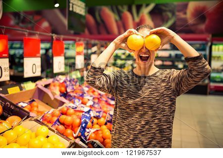 Funny woman holding grapefruit for her eyes.Young woman shopping for recipe ingredients in a supermarket having fun at the grocery shop.Self service.Choosing from variety of products and prices