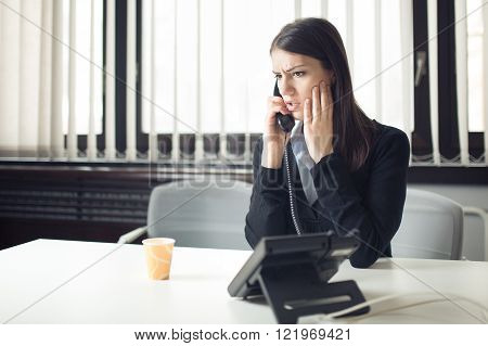 Worried stressed depressed office worker business woman receiving bad news emergency phone call at work.Looking desperate.Manager solves a problem.Dismissed woman sitting in office.Getting fired.Argue