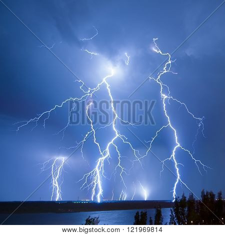 Night lightning flash over the river during a storm
