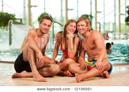 Three young people - woman and two men - at a public swimming pool standing in front of the water