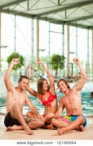 Three young people - woman and two men - at a public swimming pool, sitting on the floor having fun