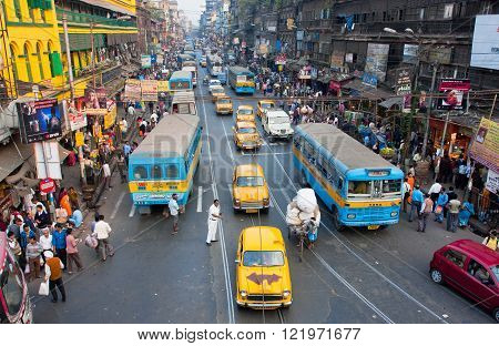 KOLKATA, INDIA - JAN 20: Antique yellow Ambassador taxi cabs down the busy street on January 20, 2013 in West Bengal. First Ambassador was produced by the Yellow Cab Manufacturing Company in 1921