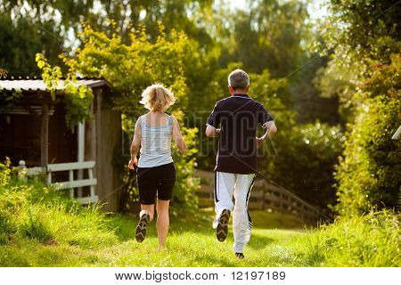 Mature or senior couple doing sport outdoors, jogging down a path in summer, the sun is low on evening