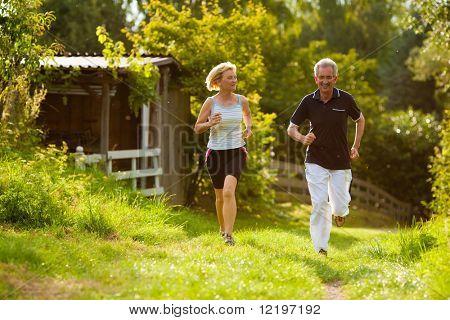 Reife oder senior paar Sport im Freien zu tun, laufen ein Weg im Sommer, ist die Sonne tief auf eveni