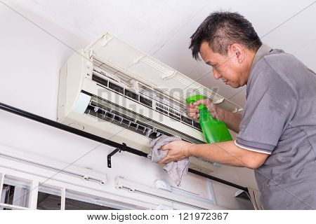 Series of technician servicing the indoor air-conditioning unit. Spraying chemical to remove deposits.