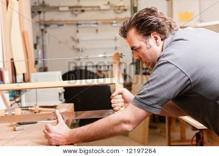 Carpenter working on a hand saw cutting boards in his workshop
