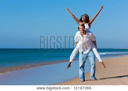 Couple in love - Caucasian man having his African-American woman piggyback on his back under a blue sky on a beach, she is stretching her arms