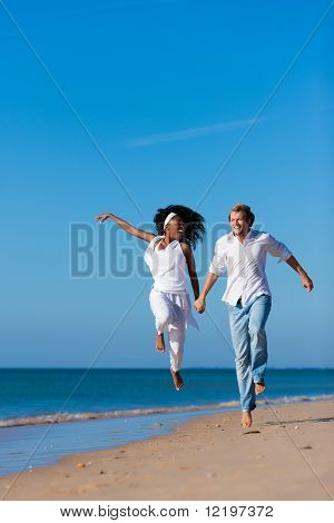 Couple - black woman and Caucasian man �¢�?�? having a walk jumping on a beach in their vacation