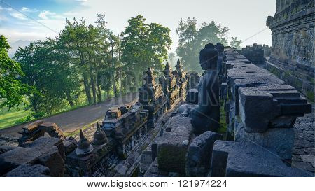 Stone Buddha Borobudur temple (Indonesia) meets sunrise.