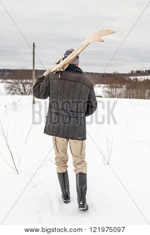villager man carries old wooden skis in the winter in the village