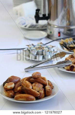 Catering banquet table with baked food snacks cakes coffee and coffee creamers self serve open buffet dinner selective focus
