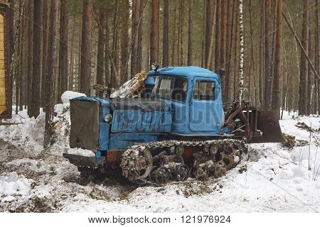 blue tractor in pine tree forest. snowy wood in taiga, track