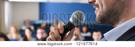 Close-up of young elegant man in suit speaking to microphone. Leading classes with students in lecture hall