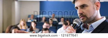 Handsome young professor leading lecture in auditorium. Close-up of man speaking to microphone to young people