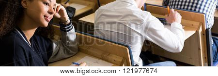 Young pretty thoughtful dreaming girl during final exam at university