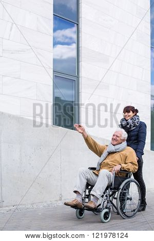Image of helpful female spending time with grandfather outdoors