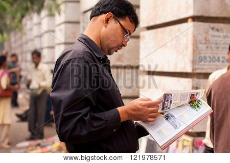 KOLKATA, INDIA - JANUARY 15: Asian man flips through a magazine on the street on January 15, 2012 in Kolkata India. From 1976 Kolkata have the biggest Book Fair with 2 million visitors every year.