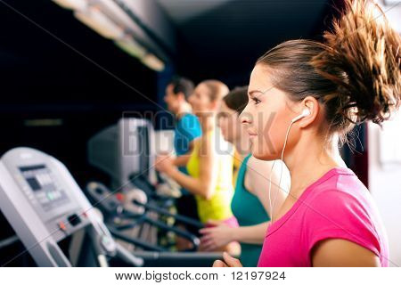 Running on treadmill in gym - group of women and men exercising to gain more fitness, the woman in front wears earplugs and enjoys music
