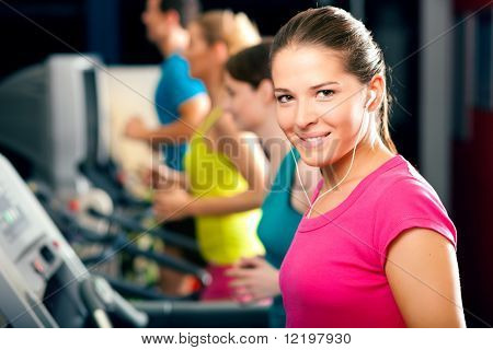 Running on treadmill in gym - group of women and men exercising to gain more fitness